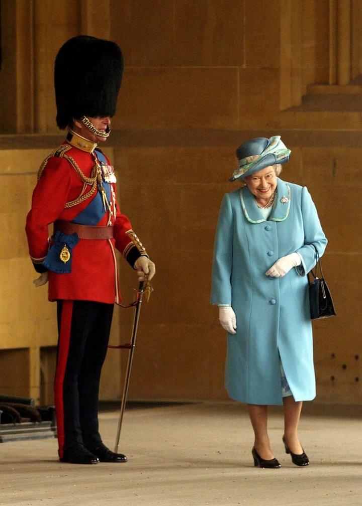 Ratu Elizabeth II tak bisa menahan senyum saat melewati Pangeran Philip yang memakai topi bulu (2005). Photo credit: Getty Images