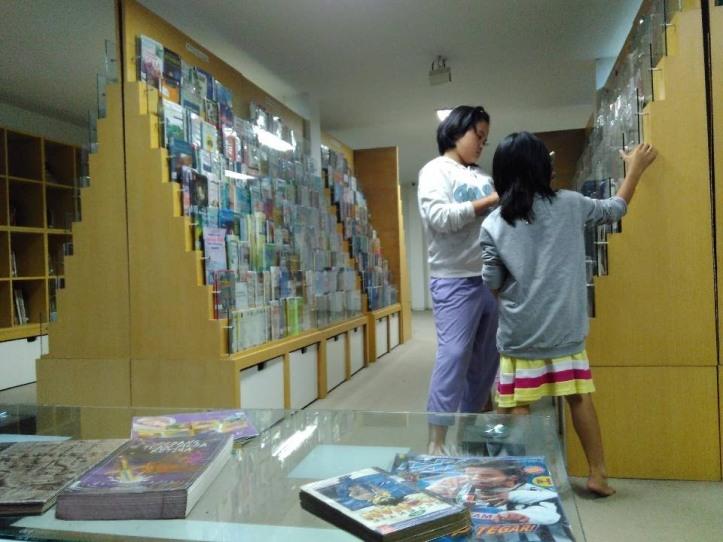 Pengunjung melihat-lihat koleksi taman baca. Photo credit: Koleksi Pribadi