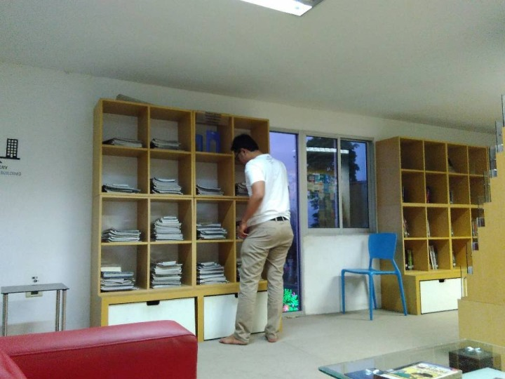 Buku dan majalah diletakkan di rak-rak kayu. Photo credit: Koleksi Pribadi